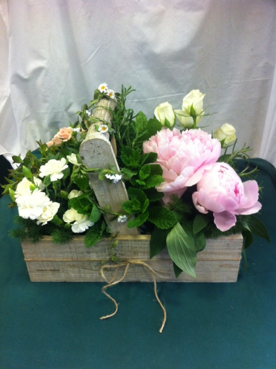 Rustic table arrangement made for colleage featuring peonies, spray roses & herbs