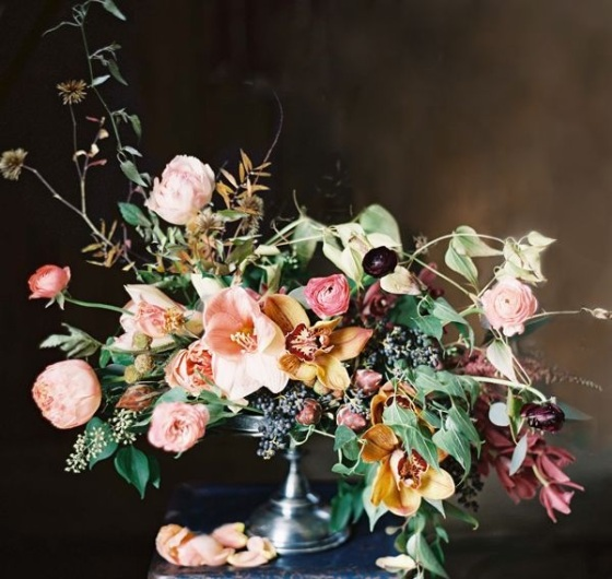 A winter centerpiece with peach Amaryllis, garden roses, and ranunculus, gold and wine-coloured orchids, plus an unruly assortment of foliage, created by Joy Thigpen  and featured on www.oncewed.com/